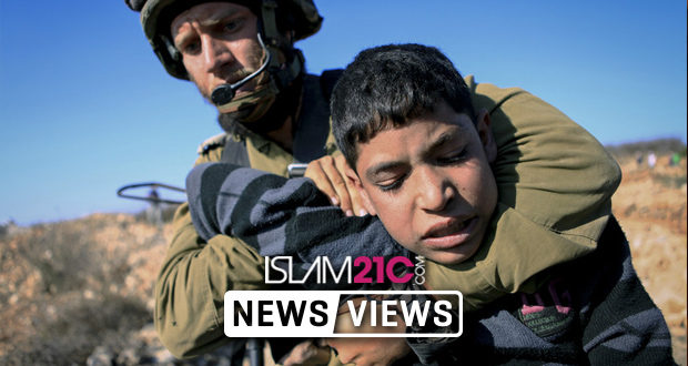 A Palestinian child held by a Zionist soldier in Israeli IDF